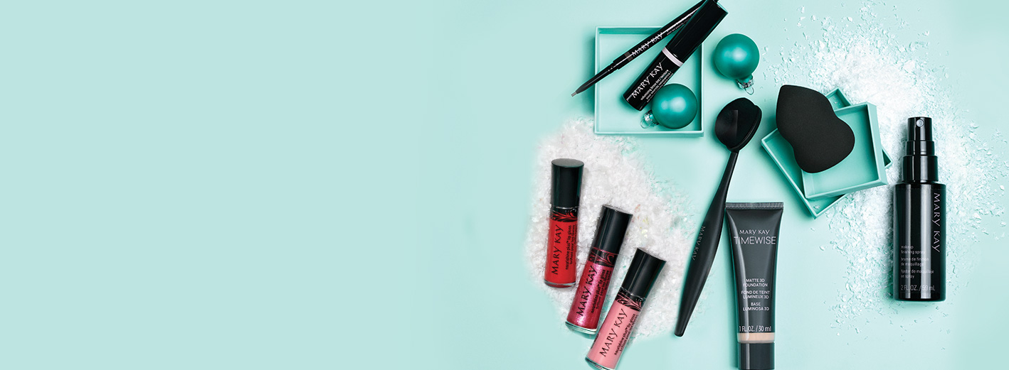 Mary Kay® holiday gifts: NouriShine Plus® Lip Gloss, Mask Applicator, Precision Brow Liner, Volumizing Brow Tint, Blending Brush, TimeWise® Matte 3D Foundation, Blending Sponge and Makeup Finishing Spray on a teal background