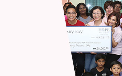 Group of people holding a large check representing Mary Kay's positive community impact.