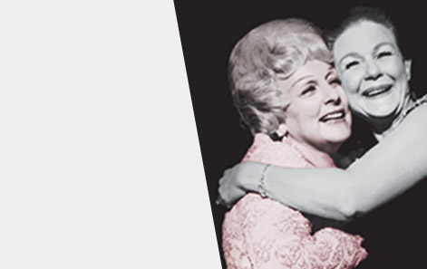 Mary Kay Ash embraces a member of the Mary Kay independent sales force in a warm hug as both women smile.