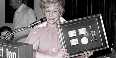Mary Kay Ash smiles for a photo while standing at a podium and holding up a plaque.