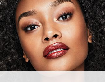 A woman is wearing a Mary Kay® ruby-hued makeup artist look featuring the contoured lip trend.