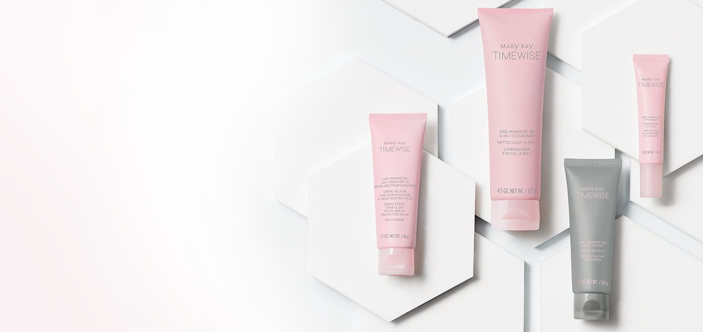 The four products from the new Mary Kay® TimeWise® Miracle Set 3D™ are shown in pink and gray tubes in front of a white hexagonal background.