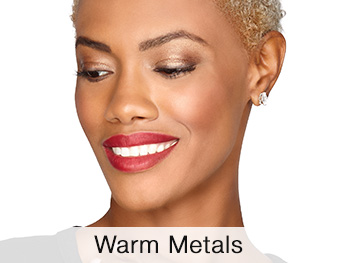 A smiling woman is wearing a Mary Kay® makeup look that features golden eye shadow shades and a berry blush and lipstick for a stunning, glowing look