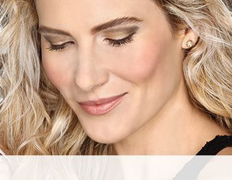 A smiling woman is wearing a Mary Kay® makeup look that features green eye shadow shades and a peachy blush and lipstick for an inspired-by-nature look.