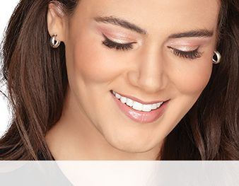 A smiling woman is wearing a Mary Kay® makeup look that features pink and mauve eye shadow shades and a nude blush and lipstick for an updated take on a neutral look.
