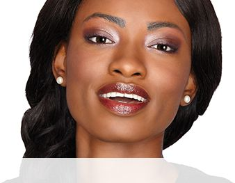 A smiling woman is wearing a Mary Kay® makeup look that features purple eye shadow shades, a coordinating blush and berry lips for a feminine look.
