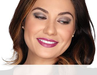 A smiling woman is wearing a Mary Kay® makeup look that features blue eye shadow shades and a neutral blush and lipstick in an all-about-the-eyes look.