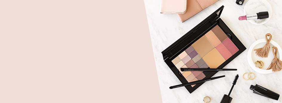 The new Mary Kay Pro Palette™ sits atop a marble countertop alongside various makeup and accessory items.