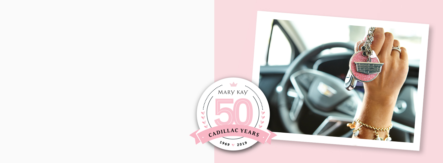 Hand holding a Mary Kay® pink Cadillac® key chain, celebrating the 50th anniversary of the pink Cadillac®