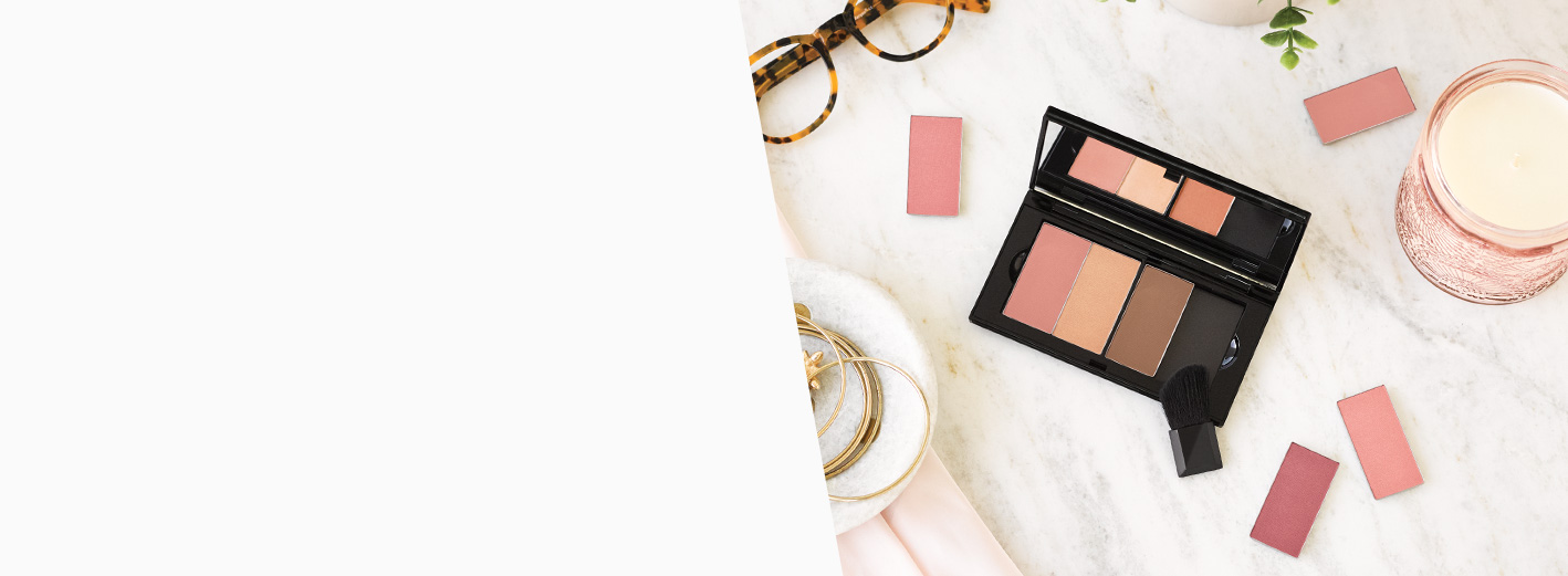 Eyeglasses, accessories, the Mary Kay Perfect Palette™ and Mary Kay® makeup products lie on a marble countertop.