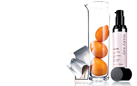 An open TimeWise Vitamin C Activating Square packet leaning on a glass tube holding three oranges next to TimeWise Tone-Correcting Serum balancing on its cap.