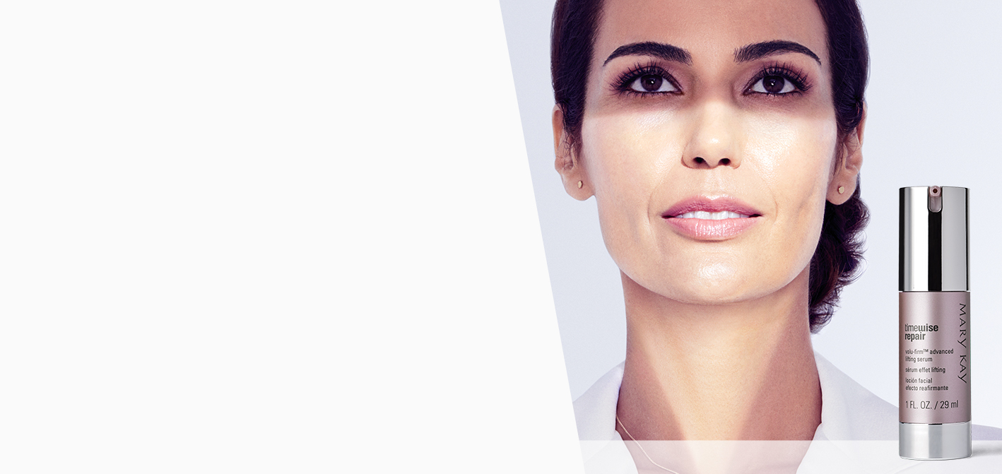 A triangle of light highlights the area of youthfulness on a brunette woman's face, and the new TimeWise Repair® Volu-Firm® Advanced Lifting Serum is shown beside her.