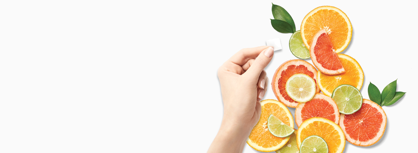Hand holding a TimeWise Vitamin C Activating Square® over citrus rounds against a white background
