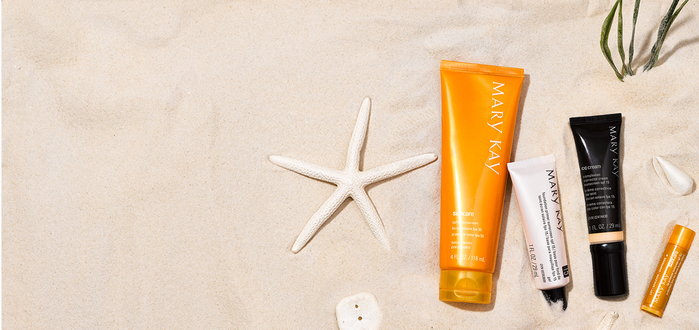 Mary Kay® Sun Care Sunscreen, Mary Kay® Foundation Primer, Mary Kay® CC Cream y Mary Kay® Sun Care Lip Protector sobre un fondo de arena y objetos decorativos de playa