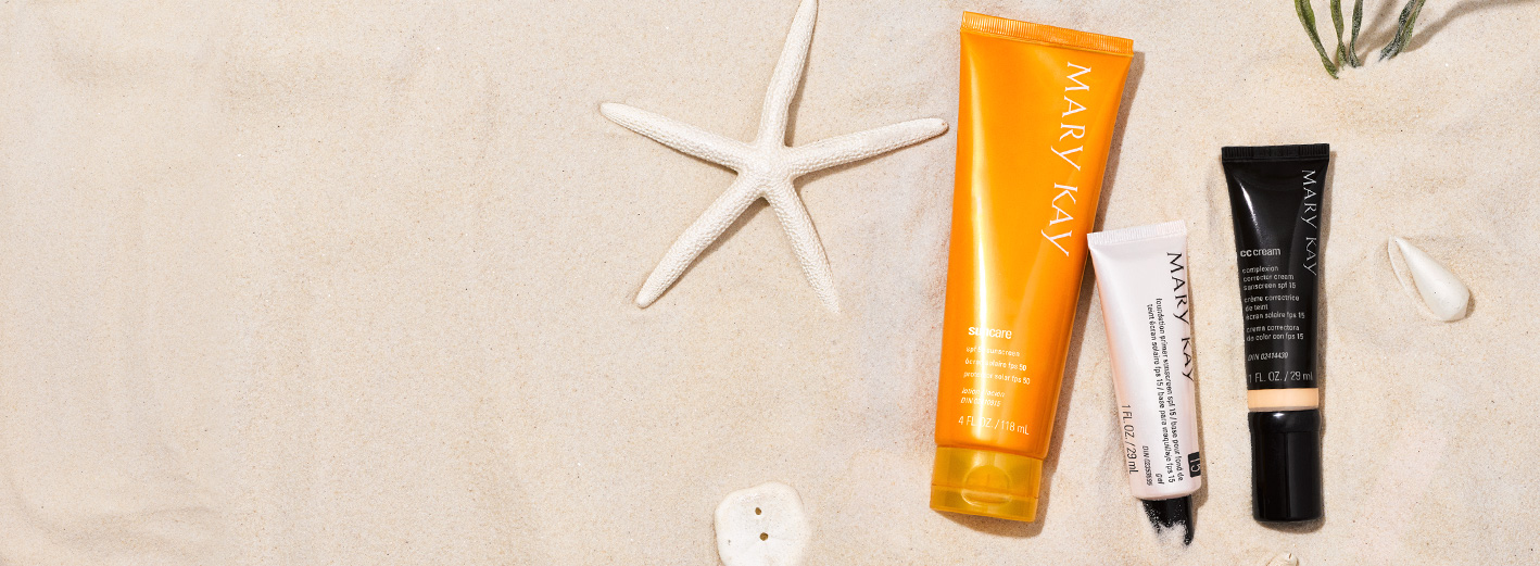 Mary Kay® Sun Care Sunscreen, Mary Kay® Foundation Primer y Mary Kay® CC Cream sobre un fondo de arena y objetos decorativos de playa
