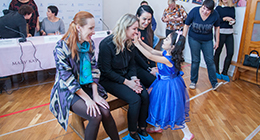 Mary Kay employees interacting with a child at a philanthropic event.