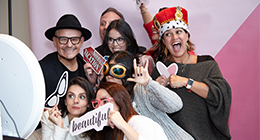 Luis Casco and Mary Kay employees wearing props and posing for a photo booth.