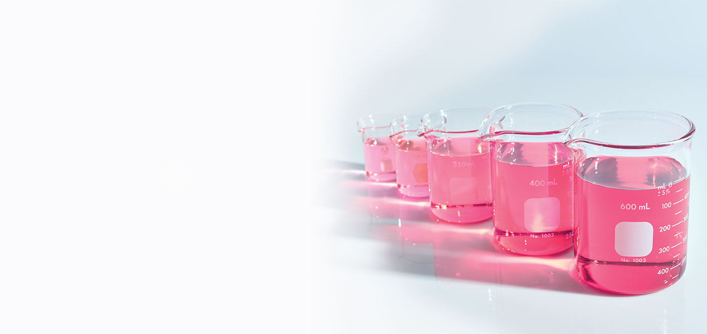 Mary Kay beakers holding pink liquids standing against a white background