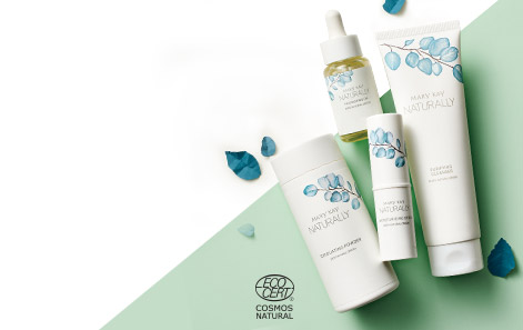 Mary Kay Naturally® products styled against a green and white background, with blue leaves sprinkled in.