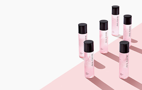 Mary Kay® Oil-Free Eye Makeup Remover bottle on pink and white background