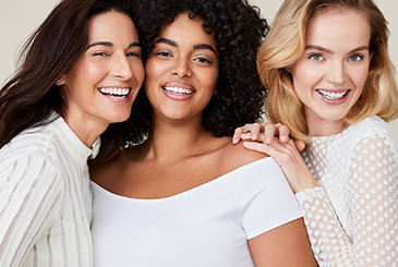 A picture of a mature Latina, a curvy black woman and a blonde white woman with glowing skin smiling and laughing