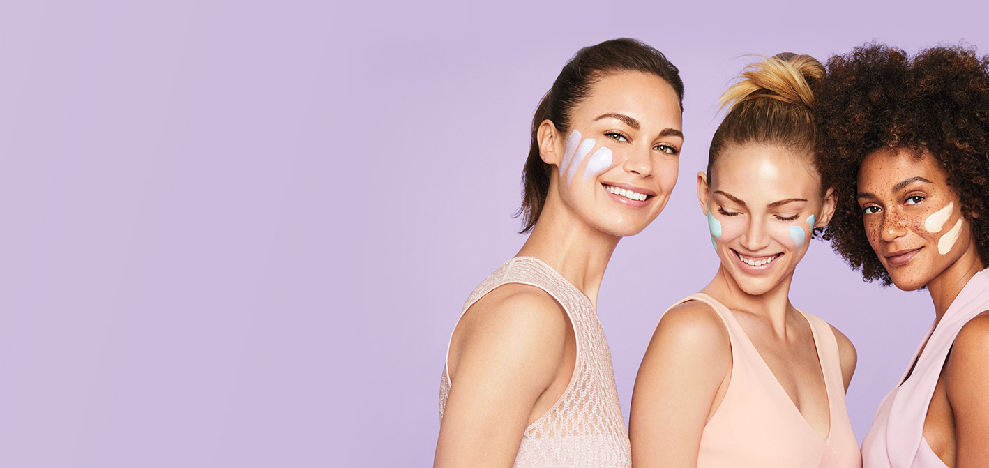 Three models of varying skin tones with smears of limited-edition Mary Kay Mad About Masking® masks on their cheeks in front of a purple background.