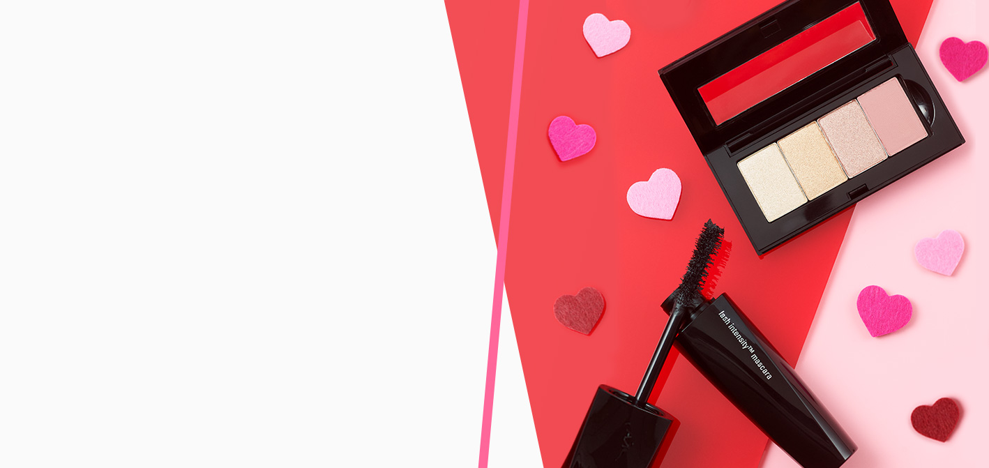 A Mary Kay Petite Palette® filled with eye shadow shades next to Lash Intensity® Mascara on a red and pink background sprinkled with hearts