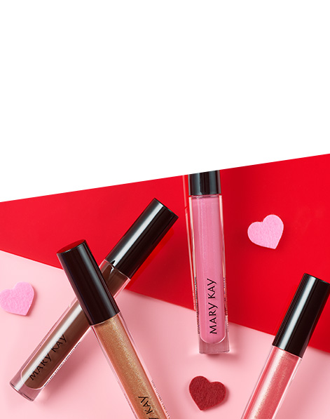 Four tube of Mary Kay® Unlimited Lip Gloss lying on a pink and red background with little hearts