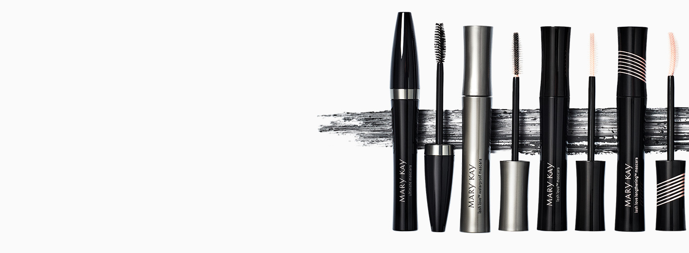 A lineup of Mary Kay® mascaras with caps off showing wands and a smear of mascara in the background