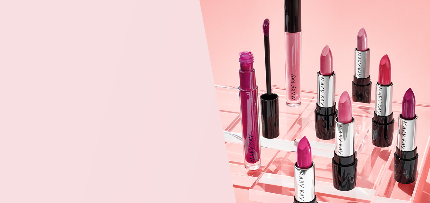A group of Mary Kay® lipsticks and lip glosses on a pink background that are photographed together with caps off to show their beautiful colors