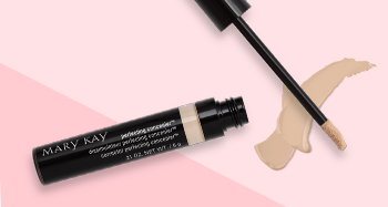 An open tube of Mary Kay® Perfecting Concealer is photographed alongside its doe-foot applicator and a product smear in front of a two-toned pink background.