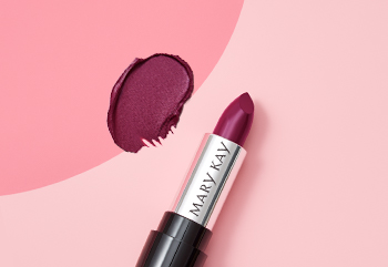 A berry-colored Mary Kay® lipstick is photographed with its cap off next to a product smear on a two-toned pink background.