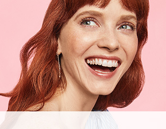 A redhead with bangs in a natural makeup look