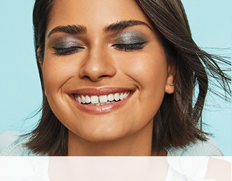 Smiling model with closed eyes wearing a Mary Kay® makeup artist look against blue background